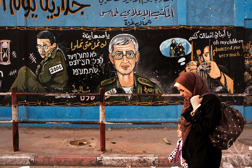 A Palestinian woman walks past a HAMAS mural depicting captive Israeli soldier Gilad Shalit now and in 30 years December 26, 2009 in the Jabaliyah Refugee Camp in Gaza.  HAMAS and Israel are reported to have been recently negotiating a prisoner exchange that would see some 950 Palestinian prisoners swapped for Shalit, who has been kept captive for more than 3 years now in Gaza.