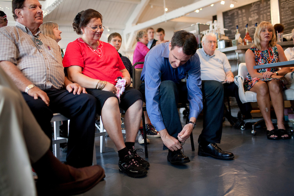 Republican presidential hopeful Tim Pawlenty, third from left, ties his shoe before a campaign event on Tuesday, July 26, 2011 in Ottumwa, IA.