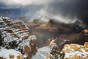 Beams of sunlight break through a the clouds at the Grand Canyon.