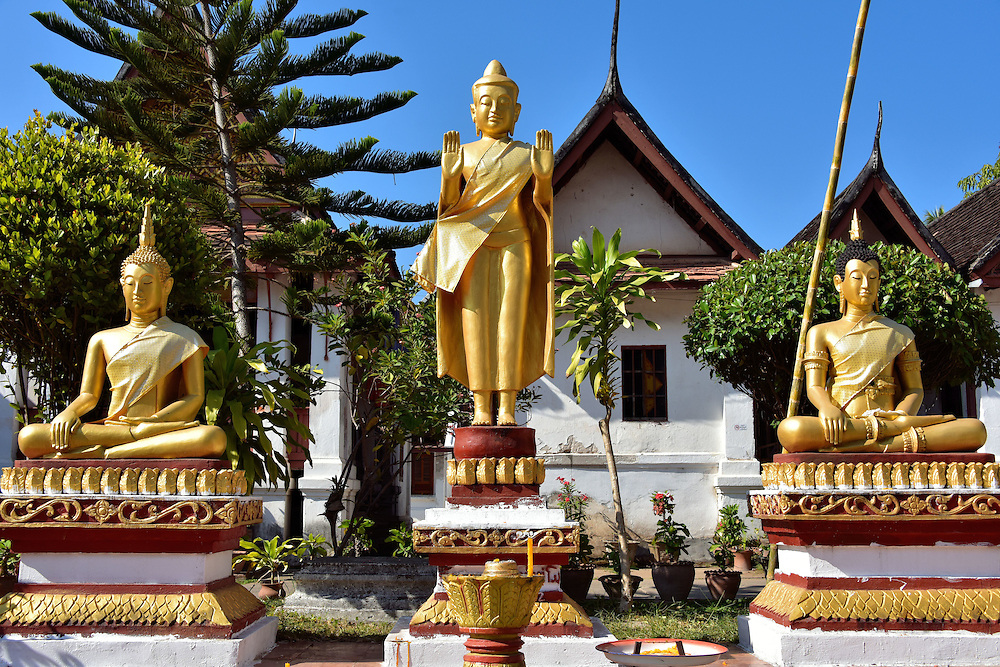 Three Buddha Statues in Courtyard at Wat Mai in Luang Prabang, Laos <br /> These three golden Buddha are in the courtyard of Wat Mai.  The one in the middle with two palms extended outward represent the Buddha &ldquo;Repelling the Waters&rdquo; and &ldquo;Preventing Relatives from Fighting.&rdquo;  On either side are Buddha statues in the &ldquo;Calling the Earth to Witness&rdquo; pose.