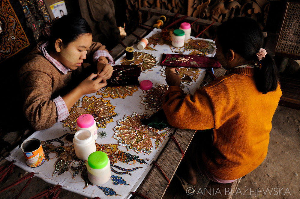 Myanmar/Burma, Mandalay. Women working in a tapestry workshop.<br /> Tapestry handicrafts are very popular souvenirs from Myanmar.