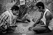 Waiting for the broken truck to be repaired, three men draw a checker board on the roadside and play a local game.