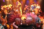Zwei junge Punkerinnen mit Irokesen-gestylten Haaren umarmen sich bei einem Live-Konzert. Two  young punks with iroquois styled hairs embrace each other  in a concert.