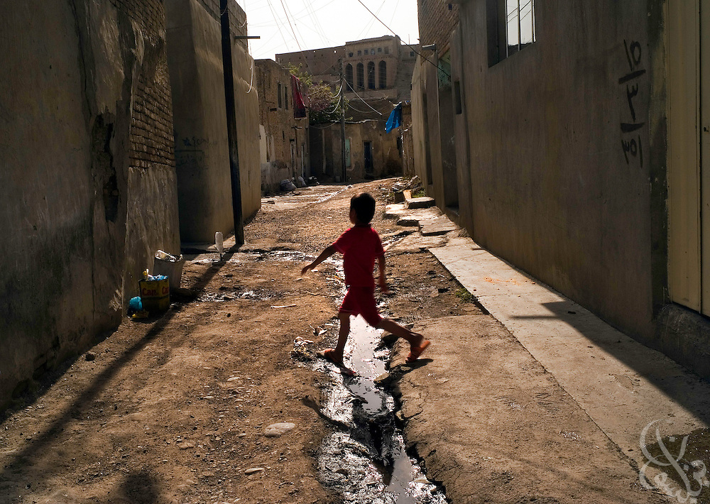 A Kurdish boy walks down a narrow alley with an open sewer line running down it May 23,2007 in an older neighborhood of Erbil, Iraq. Despite a wave of new investment projects in Kurdistan, the region's infrastructure including water and electric systems remains woefully underdeveloped.  .