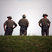 Left to right, State Troopers Damon Williams and Edward Valdez of Canton and Matt Kuhlengel of Clarksville look out over the Sabine Pass Ship Channel in Port Arthur, Texas, Thursday September 18, 2008.  The men are on duty watching for looters throughout the coastal region affected by Hurricane Ike.