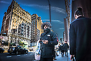 man in a hooded coat walking on the Upper West Side of New York City
