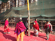 05 MARCH 2017 - KATHMANDU, NEPAL: Nepalese gather around a holi pole set up for the Hindu holiday of Holi on Durbar Square. The scaffolding is holding up the wall of the Hanuman Dhoka Palace on Durbar Square in Kathmandu, a UNESCO World Heritage Site badly damaged in the 2015 earthquake. Much of Kathmandu is now a construction site because of rebuilding  two years after the earthquake of 25 April 2015 that devastated Nepal. In some villages in the Kathmandu valley workers are working by hand to remove ruble and dig out destroyed buildings. About 9,000 people were killed and another 22,000 injured by the earthquake. The epicenter of the earthquake was east of the Gorka district.     PHOTO BY JACK KURTZ