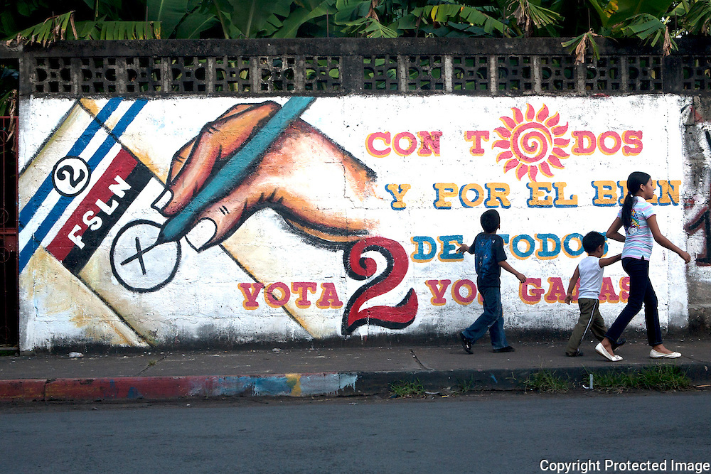 Children walk by a sign showing people how to vote for Ortega in the Elections, Alta Gracias, Ometepe, Nicaragua.