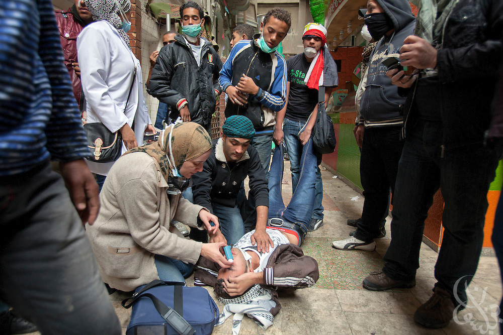 Egyptian protestors treat a wounded colleague after he was overcome by tear gas fired by the police during ongoing demonstrations November 20, 2011 near Tahrir square in central Cairo, Egypt.  Protestors demanding the transition of power from military to civilian control clashed with Egyptian security forces for a second straight day in central Cairo, with hundreds injured and at least 11 protestors killed.  (Photo by Scott Nelson).