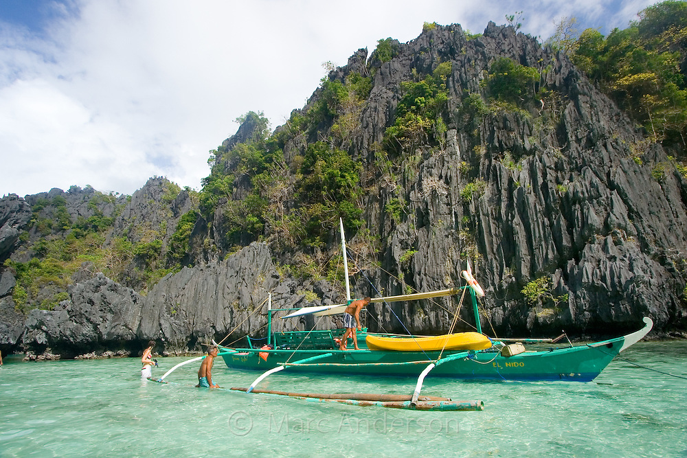 Boat moored at the entrance to Small Lagoon surrounded by limestone cliffs in the Bacuit Archipelago, El Nido, Palawan, Philippines.