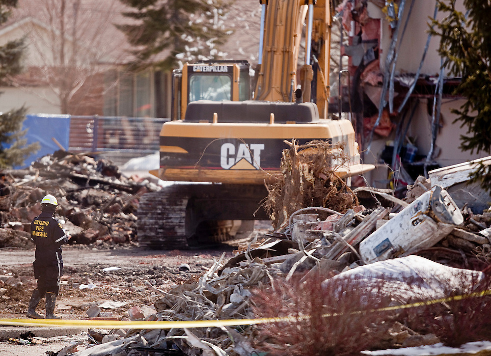 Investigators from the Ontario Fire Marshal's office and the Police examine the rubble of an apartment building in Woodstock Ontario, Wednesday, March 30, 2011. The building exploded Sunday morning leaving 2 residents missing and presumed dead.<br /> THE CANADIAN PRESS/ Geoff Robins
