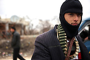 A young member of the Free Syrian Army with a belt of selfmade bullets. Province of Idlib, Syria.