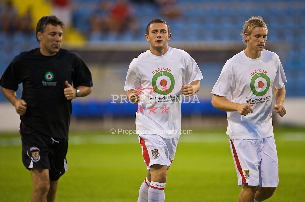 PODGORICA, MONTENEGRO - Wednesday, August 12, 2009: Wales' Neal Eardley and Jack Collison warm-up wearing a shirt in support of former captain John Hartson who is battling against cancer, and to promote awareness of men's health issues with web site checkemlads.com, before an international friendly match against Montenegro at the Gradski Stadion. (Photo by David Rawcliffe/Propaganda)