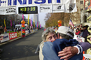 80 Year old Helen Klein gets a hug from her husband Norman Klein after she shattered the world record for 80 year women with a time of 4:31 at the During the California International Marathon, Sunday Dec. 8, 2002, in Sacramento. Her husband Norman Klein joined her at the last part of the race to cross the finish line together.