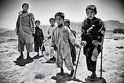 An Afghan boy, who lost his leg as he tried to find a piece of metal to make money, stands with his friends neaar Bagram air base.