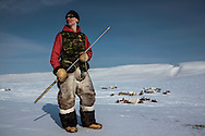 Inuit Canadian Ranger Wally poses with his seal hunting harpoon as he wears ancestral caribou's skin pants along his Ranger's uniform on Cornwallis  Island during Nunalivut 2012 sovereignty exercise by Canadian Forces in arctic Canada.