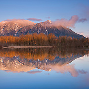 A snow storm clears at the summit of Mount Si, a 4,167 foot (1,270 meter) mountain in the Cascade Range near North Bend, Washington. Mount Si, covered in a light dusting of fresh snow, is reflected in Borst Lake.