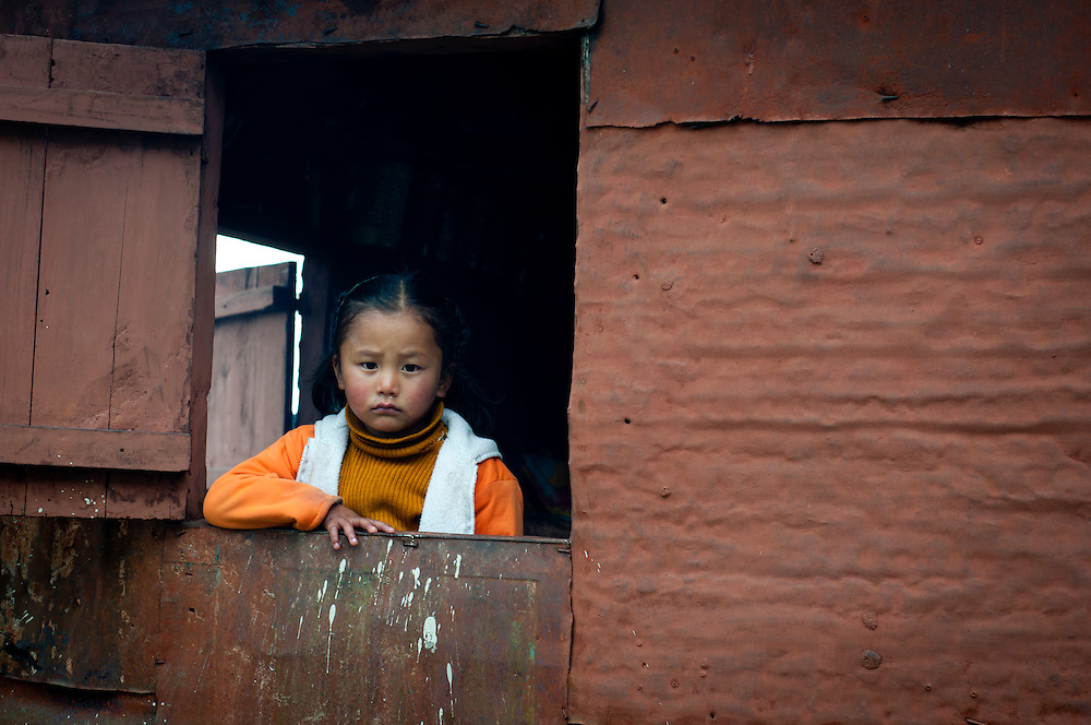 In a remote, impoverished agricultural village in India, a girl gazes out from a window in her home,