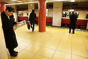 Businessmen waiting on a platform at Shimbashi station