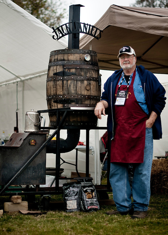 Dusty Bridges from the team Swine & Wine Cookers  is a retired building contractor from Ringgold, Georgia. He built his own barbecue pit from a wood stove he found at a yard sale and an old whiskey barrel. ..Jack Daniels Invitational Barbecue 2012 - The Jack. .Photographer: Chris Maluszynski /MOMENT