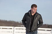 handsome man walking outdoors in a leather jacket during the winter