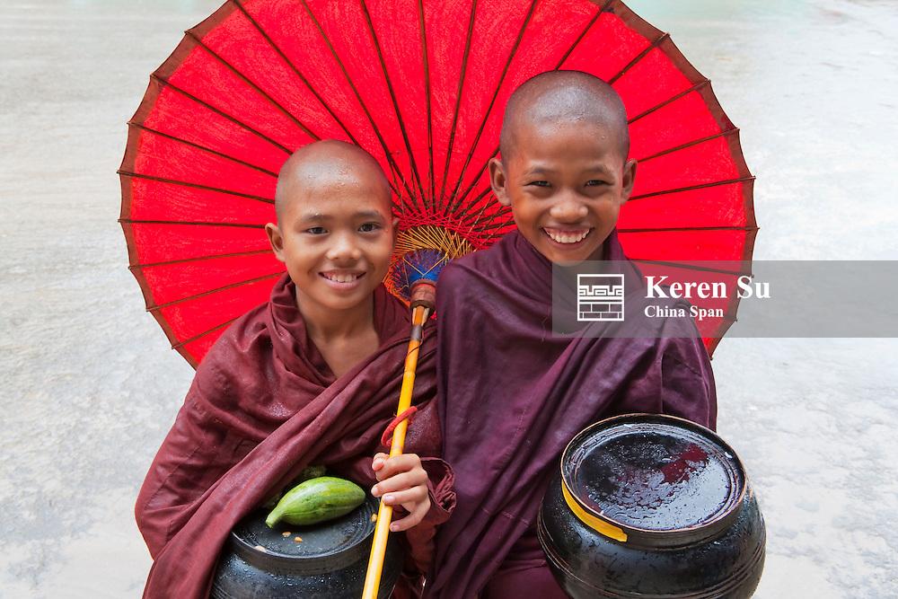 Novice monks holding alms woks with red umbrella, Bagan, Myanmar
