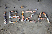 Ibiza written on the sand with assorted stones
