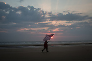 A man is seen carring an American flag at the exact hour f the beging of the allied invasion on Omaha beach celebrating the 69th anniversary of the D Day