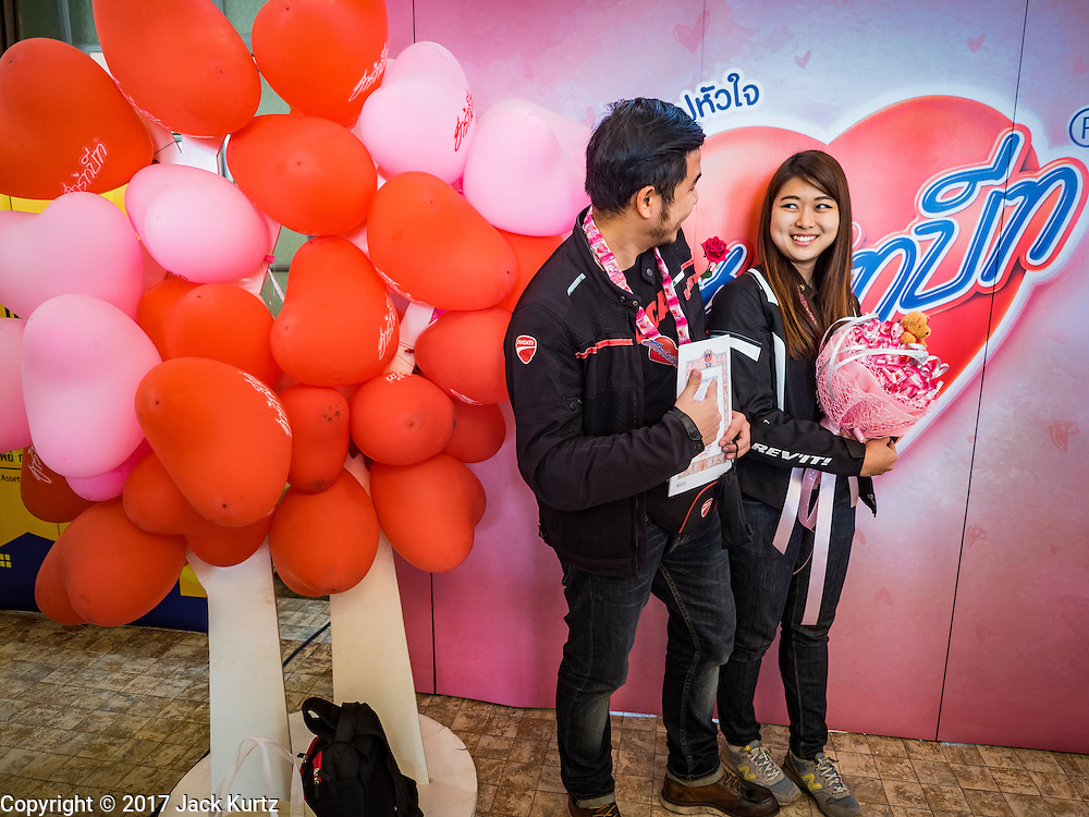 """14 FEBRUARY 2017 - BANGKOK, THAILAND: A couple waits to have their picture taken during mass weddings in the Bang Rak district in Bangkok. Bang Rak is a popular neighborhood for weddings in Bangkok because it translates as """"Village of Love."""" (Bang translates as village, Rak translates as love.) Hundreds of couples get married in the district on Valentine's Day, which, despite its Catholic origins, is widely celebrated in Thailand.      PHOTO BY JACK KURTZ"""