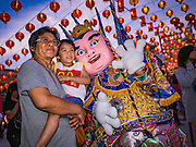28 JANUARY 2017 - SAMUT PRAKAN, SAMUT PRAKAN, THAILAND: A Thai family poses for photos with an entertainer at the Chinese New Year Lantern Festival at the Tham Katanyu Foundation shrine in Samut Prakan, a suburb about 15 miles from Bangkok. More than 5,000 handmade lanterns imported from Taiwan are hung on the grounds of the shrine. Some of the lanterns are traditional Chinese lanterns, others are in the shapes of people or deities. There is also traditional Chinese entertainment, likes lion dances, at the festival.     PHOTO BY JACK KURTZ