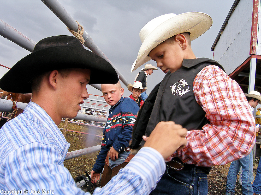 "30 JULY 2005 - WILLIAMS, ARIZONA, USA: A cowboy talks his little brother, who was competing in steer riding, behind the chutes at the Arizona Cowpunchers' Reunion Rodeo, the largest amateur rodeo in Arizona, in Williams, AZ, July 30. Professional rodeo cowboys cannot participate in the rodeo. Only working ranch cowboys and their families can participate in the rodeo, which features sports more geared to ranch life, like ""wild cow milking"" than pro rodeos, which feature bull riding. Williams, a small ranching town in northern Arizona and about an hour from the south entrance to the Grand Canyon National Park, has reinvented itself as a tourist destination. The town draws tourists going to the park and tourists who want to experience American western lifestyle. The town hosts the largest amateur rodeo in Arizona drawing contestants and spectators from across the state. PHOTO BY JACK KURTZ"