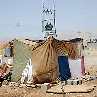 A Syrian refugee makes his way past a tent outside of a makeshift refugee camp in Arbat, outside Sulaimaniya in Iraqi Kurdistan, Monday, September 2, 2013. September 2013.