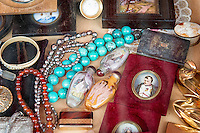 Jewelry, bracelets necklaces, old photos, assorted knickknacks in a case at the flea market in Nice, France