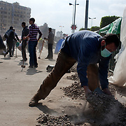 Egyptian volunteers pick up garbage and rubble left over from 18 days of protest in the area around Tahrir Square February 12, 2011 in Cairo, Egypt. The day after the revolution toppled the regime of President Hosni Mubarak, Egyptians continued to celebrate and began to focus on rebuilding their city and society. (Photo by Scott Nelson)