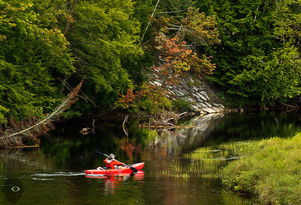 A canoeist paddles along a quiet river inlet in Old Forge, New York.
