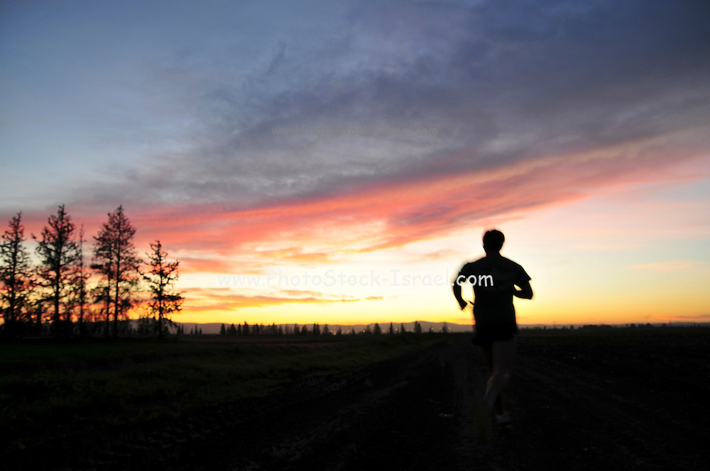 silhouette of a man jogging alone at sunset