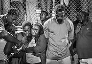 Shana Boyd, center left, and Olympic sprinter Tyson Gay, center right, stand surrounded by those gathered during a candlelight vigil at Lafayette High School for their daughter, who died in an exchange of gunfire early Sunday morning, in Lexington, Kentucky, October 17, 2016.  REUTERS/Bryan Woolston