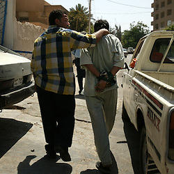 Iraqi police are seen arresting a suspect outside the Al Dulaimi Hotel in Baghdad, Iraq, Aug. 4, 2003.  Police searched for the kidnappers for 12 days resulting in the arrest of four people in connection with a kidnapping ring. Inside the home of two of the suspects, a woman and man were found tied with restraints, as well as an undisclosed amount of cash and weapons. According to police, the kidnappers were asking for $5000 for the release of the victims. The woman appeared to have been tortured. Kidnapping has been on the rise as the city is still in chaos, Iraqi police are still in training with U.S. forces and continue to fight the increasing crime.