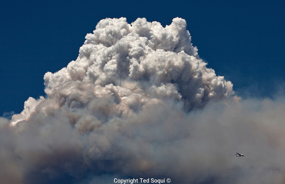 A plume of ash rises to around 20,000 feet..The Station fire burns in the hills above Los Angeles. The city has experienced above normal summer temperatures and low humidity. This is a fuel driven fire, no Santa Ana winds are expected till late September