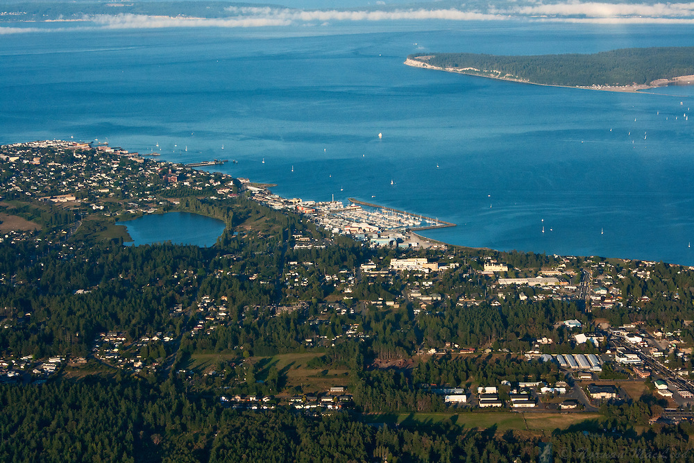Early evening arial view of Port Townsend Washington after a warm summer day, with Fort Flagler State Park on Marrowstone Island in the background.