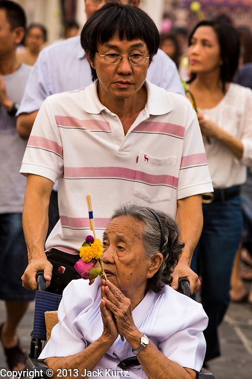 """25 FEBRUARY 2013 - BANGKOK, THAILAND: Thai woman in a wheelchair bows her head as she enters Wat Benchamabophit Dusitvanaram (popularly known as either Wat Bencha or the Marble Temple) on Makha Bucha Day. Makha Bucha is a Buddhist holiday celebrated in Myanmar (Burma), Thailand, Cambodia and Laos on the full moon day of the third lunar month (February 25 in 2013). The third lunar month is known in Thai is Makha. Bucha is a Thai word meaning """"to venerate"""" or """"to honor"""". Makha Bucha Day is for the veneration of Buddha and his teachings on the full moon day of the third lunar month. Makha Bucha Day marks the day that 1,250 Arahata spontaneously came to see the Buddha. The Buddha in turn laid down the principles his teachings. In Thailand, this teaching has been dubbed the 'Heart of Buddhism'.      PHOTO BY JACK KURTZ"""