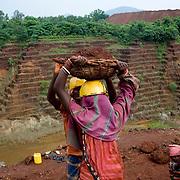 Workers carry chromite-ore to trucks at the Kamardha chromite mine. Sukinda, Orissa, India