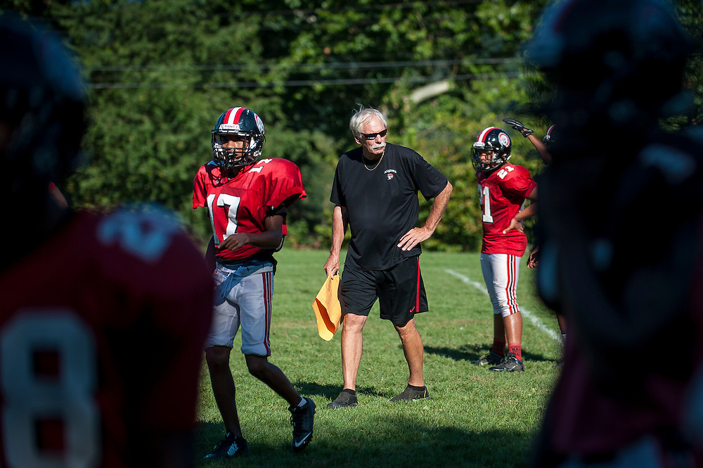 Aliquippa head coach Mike Zmijanac works with his team in preparation for their upcoming homecoming game.<br /> <br /> Zmijanac has never played a down of organized football but he is the winningest coach of what is said to be the best high school program in the region. <br /> <br /> Due to the obstacles of violence and drugs in Aliquippa, Zmijanac says that he loses six or so of his players to the pull of the street each year. And although he will not hesitate to suspend a star player, he maintains an open-door policy if they want to come back, believing that everyone deserves a second chance and that he can't give up on them.<br /> <br /> The school has one of the smallest enrollments in the Western Pennsylvania Interscholastic Athletic League (WPIAL) with the class of 2013 having only 58 kids, including 28 boys.<br /> <br /> Technically, they could play against Class A completion but they elect to play at the AA level.<br /> <br /> Pretty steep obstacles for a coach and team to overcome, but the team averaged 10 wins a year for the past 30 years. Last year Aliquippa played in its 25th WPIAL championship game, the most of any school in the district and they have won a record 15 titles. 2014 was the seventh year in a row that the Quips were in the final, also a record.<br /> <br /> The team was the training ground to NFL greats like Mike Ditka, Sean Gilbert, and Ty Law, all of whom were Aliquippa graduates.