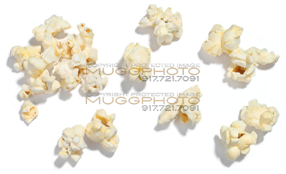 Popped popcorn kernels on white background.