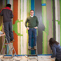 (Center) Harmony Project Director David Brown. Harmony Project volunteers paint a mural in their new offices located in the King Lincoln Theatre.(Jodi Miller)