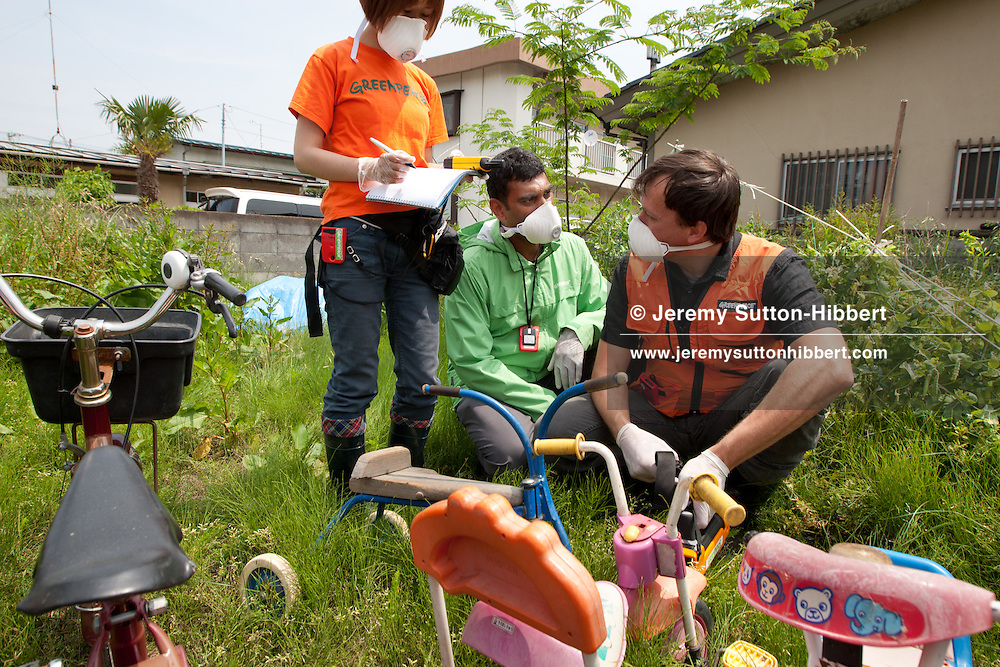 Kumi Naidoo Executive Director of Greenpeace International (wearing green jacket) observes as a Greenpeace team led by Jan Beranek (wearing orange vest and holding gammaspectrometer), undertakes radiation contamination monitoring outside the grounds of 'Soramame' children's nursery, in Fukushima city, in Fukushima prefecture, Japan, on Tuesday 7th June 2011. The city of Fukushima has been contaminated by radioactive fallout from the ongoing crisis at the Fukushima Daiichi nuclear plant. Within Fukushima city the local authorities are now undertaking a clean up of soil from school and nursery school playgrounds.