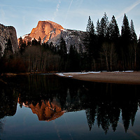 Winter scenes in Yosemite Valley located in the Yosemite National Park..Half Dome with afternoon light reflecting in the Merced River..