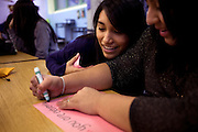 Elvira Quintero, 17, center and Denise Siguencia, 17, far right, write affirmative posters during Girls Inc Leadership class at Central Park East High School in New York, NY on November 15, 2012. Beyond sheer physical safety, a look at how schools and sitricts can create classroom conditions in which students are able to engage enthusiastically and without emotional fear of stepping forward. Photographer: Melanie Burford/Prime
