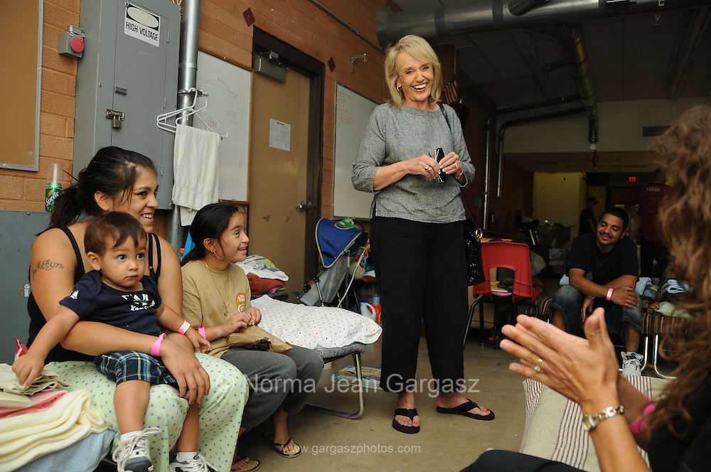 Arizona governor, Jan Brewer, visits with 15-month-old Omar Gonzalez, (left), his mother, Jackelyn Calon, his aunt, Jazlynn Sotelo, 10, his father, Gary Gonzalez, and grandmother, Patricia Rayak, evacuees of the Monument Fire who are being sheltered at Apache Middle School in Sierra Vista, Arizona, USA.
