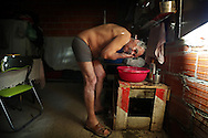 With no electricity and no bathroom Manuel bathes using water heated with a small gas bowl.